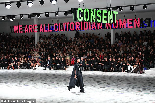 The Dior catwalk transformed into the ultimate path to female solidarity as models stormed the runway, illuminated against the backdrop of a series of feminist slogans in Paris today