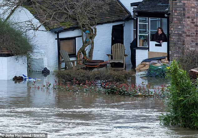 A woman looks out at flooding around a property in Ironbridge, Shropshire, today which has sandbags by the door