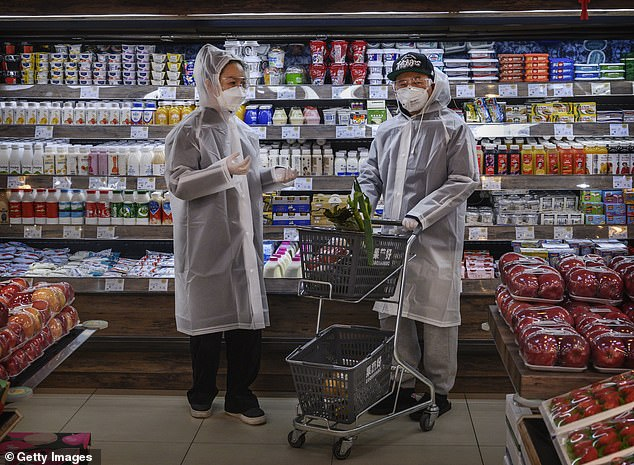 A Chinese couple in protective masks and plastic coats shop in Beijing on February 11th. A survival expert said buyers in Australia should start preparing their cabinets for a food shortage