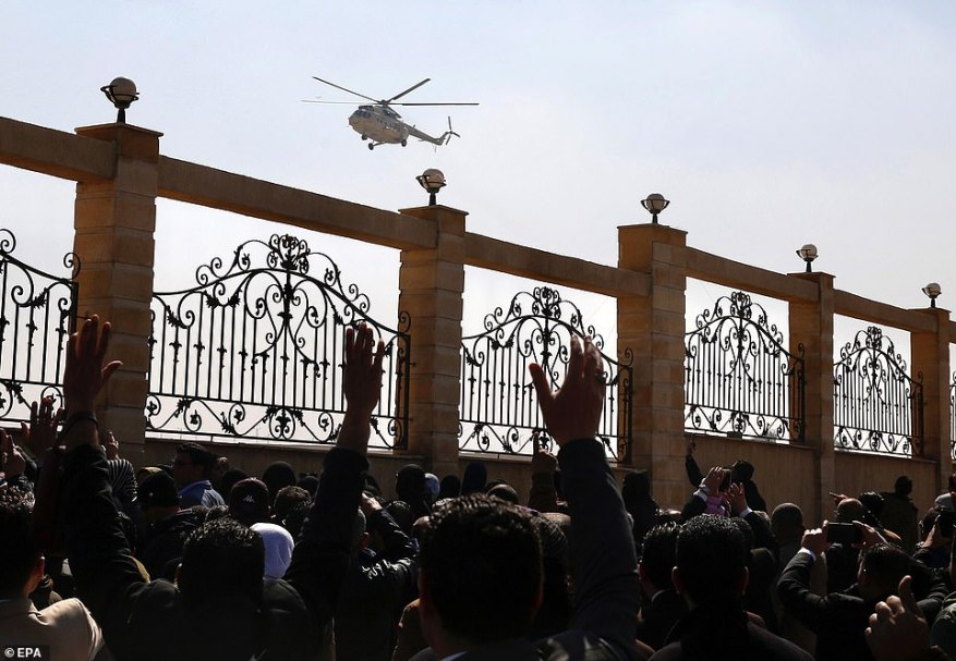 People wave at a helicopter as it lands outside Mosheer Tantawy mosque where the funeral of late former Egyptian President Hosni Mubarak took place on Wednesday