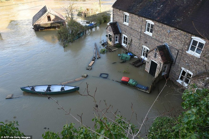 A canoe outside a flooded home in Ironbridge today as Shropshire faces severe flooding along the River Severn