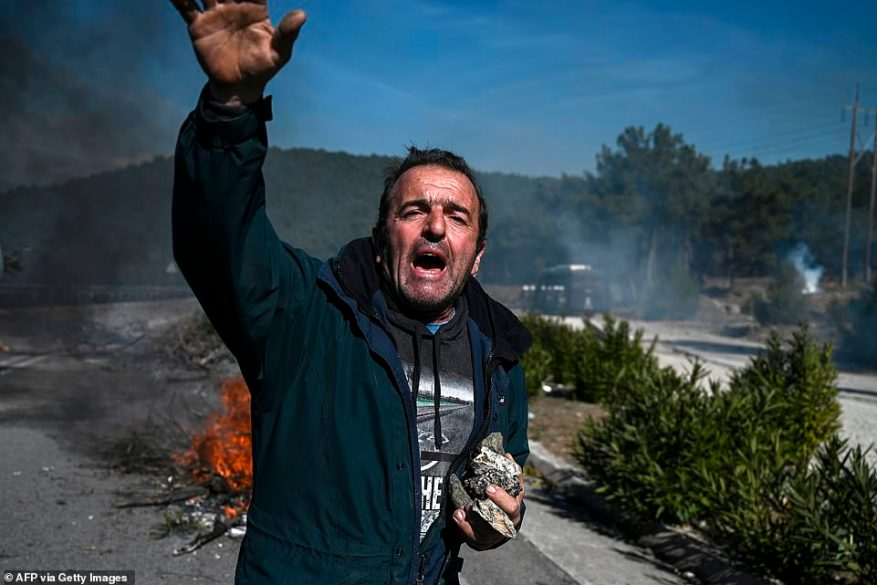 Protesters threw rocks, lit fires and kicked back gas canisters thrown by police as the clash escalated. A man gestures as he hold stones during clashes with Greek anti-riot police