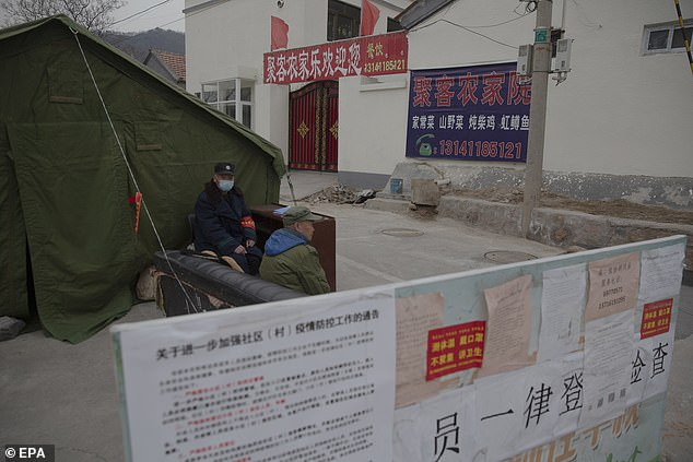 Cities around China have imposed quarantine measures in an effort to curb the outbreak. Villagers are pictured wearing masks and guarding at a checkpoint in rural Beijing, China