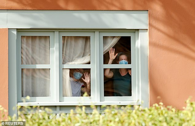 Two hotel guests wearing masks wave from the window of the Tenerife resort today where holidaymakers will have to stay put for 14 days