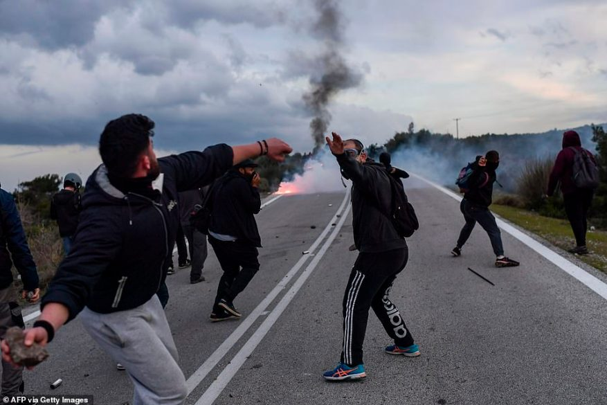 A demonstrator throws a stone toward riot police officers during protests against the construction of a new controversial migrant camp near the town of Mantamados on the northeastern Aegean island of Lesbos