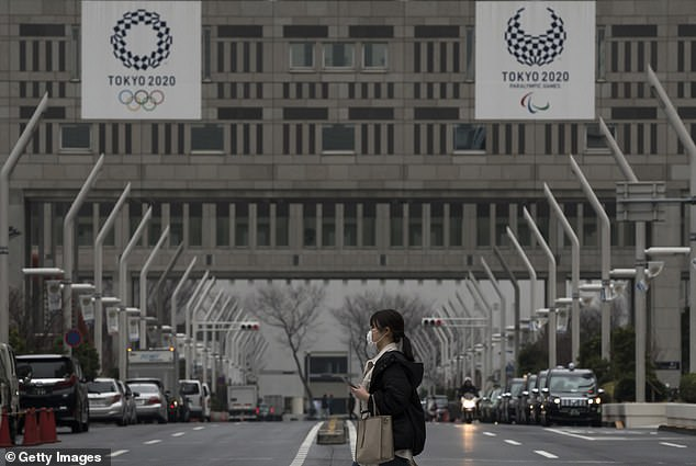 A female pedestrian crosses a busy road in Japan beneath banners promoting the upcoming Tokyo 2020Olympic and Paralympic Games. Concerns the competition may have to be cancelled are spreading as infected cases continue to rise