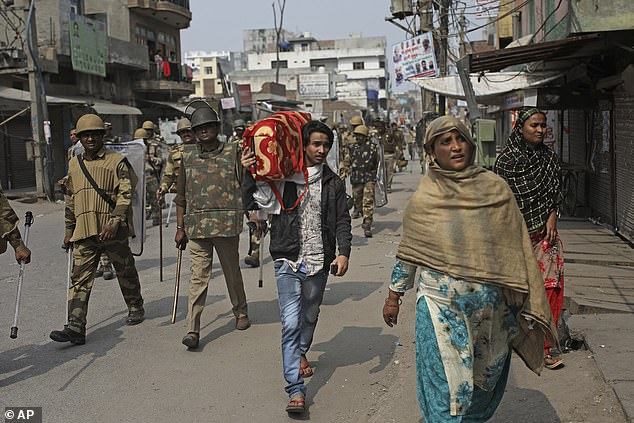 An Indian Muslim family leaves the area as Indian paramilitary soldiers patrol a street vandalized in Tuesday's violence in New Delhi, India today