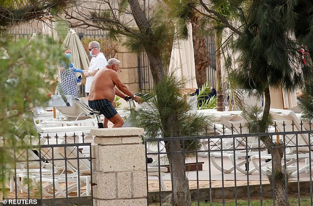 Tourists next to the outdoor pool today at the H10 Costa Adeje Palace where most guests have been allowed out of their rooms