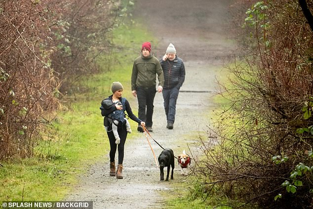 Meghan Markle is pictured above taking her two dogs for a walk with baby Archie with Canadian security guards