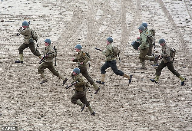 Action-packed: Extras filmed fight scenes on a beach in Devon as production gets underway for Colin Firth and Kelly Macdonald's new war epic Operation Mincemeat on Wednesday