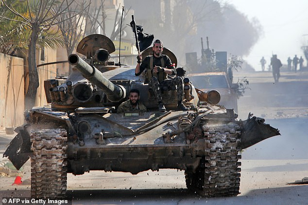 Turkey-backed Syrian fighters ride a tank in the town of Saraqib in the eastern part of the Idlib province in northwestern Syria