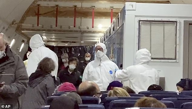 In this image from a video taken on Monday, Feb. 17, 2020, U.S. passengers who evacuated off the quarantined cruise ship the Diamond Princess and officials wait for the takeoff of a Kalitta Air airplane bound for the U.S., at Haneda airport in Tokyo