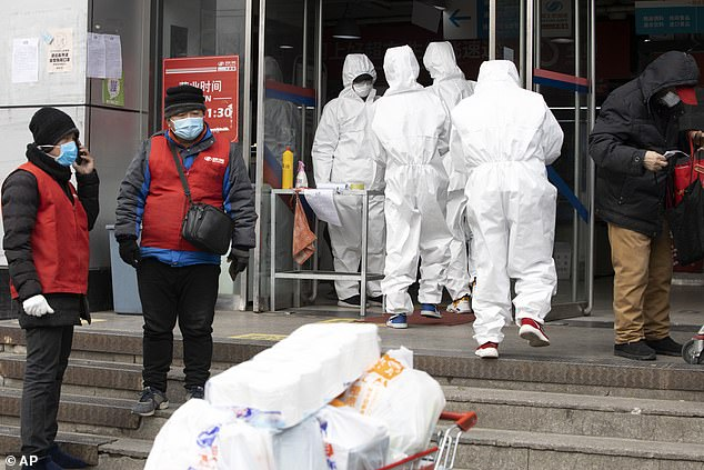 Workers in protective overalls enter a supermarket in Beijing yesterday, with new coronavirus infections now tapering off in mainland China