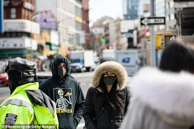 Pedestrians wearing protective masks while walking along a street in New York last week