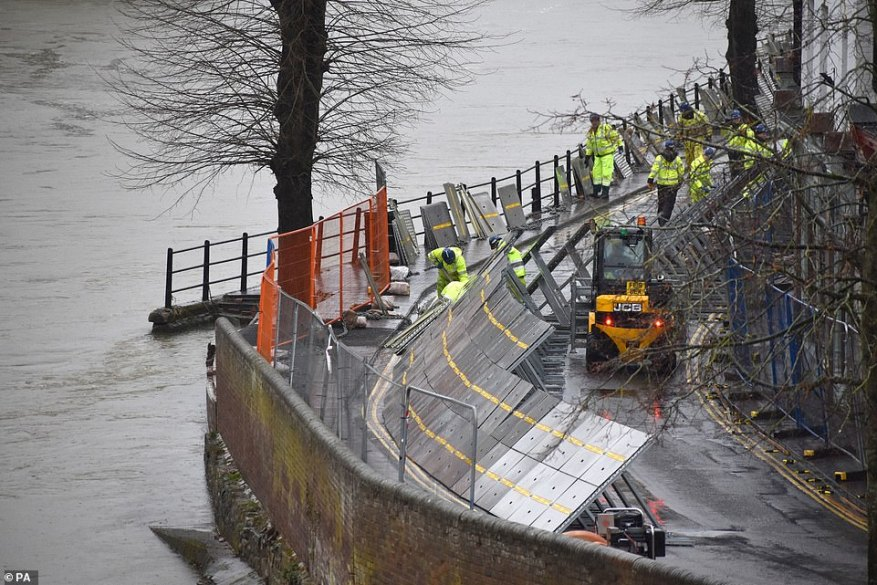 Already flooded communities are preparing for yet another deluge in what is the third storm this month. Pictured: Environment Agency teams work on temporary flood barriers in Ironbridge, Shropshire, after floodwaters receded following an emergency evacuation earlier this week