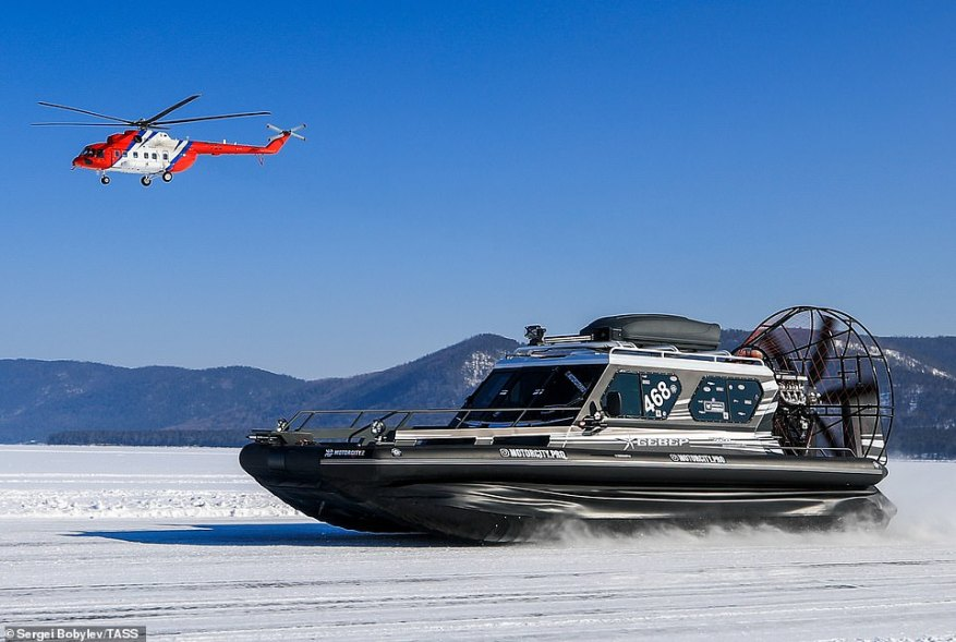 The competition in the village of Maksimikha can reach temperatures of -40C. Pictured: A helicopter races a boat on the frozen lake