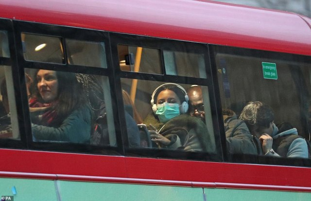 A woman wearing a face mask on a bus in London, where at the capital's flagship hospital the UK's 20th case is being treated