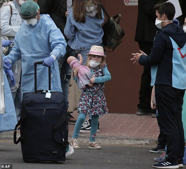Comfort: A masked girl holds her doll outside the H10 Costa Adeje Palace hotel in Tenerife, yesterday. It was put on lockdown after four Italians tested positive for coronavirus. While at least 50 Britons were free to head home, airlines have refused to fly them back to the UK