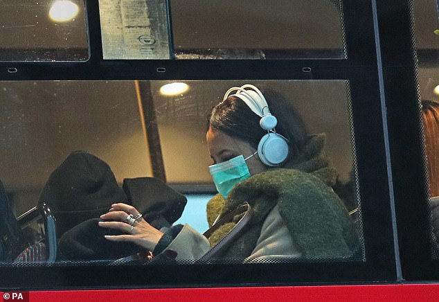 Britain's 20th coronavirus case has tonight been confirmed - after a British man who was on board the Diamond Princess cruise ship died in Japan earlier today. Pictured: A woman wearing a face mask on a London bus