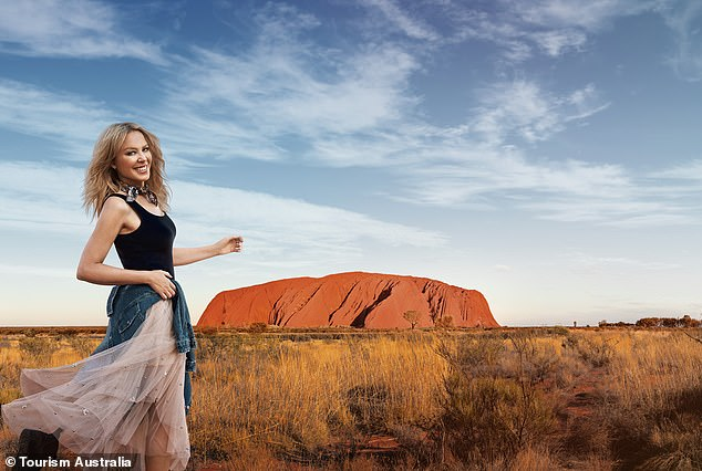 Back in business: According to Tourism Australia, most Australian tourist destinations are not impacted by bushfires. Pictured is Uluru rock and Kylie Minogue, who was heartbroken by the fires
