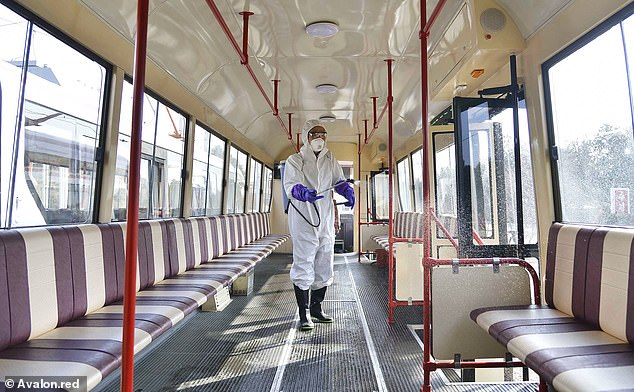 Deep cleaning: A worker in a protective suit disinfects a tram car in Pyongyang, North Korea, on February 26. Symptoms of Covid-19 are a fever, a cough or trouble breathing