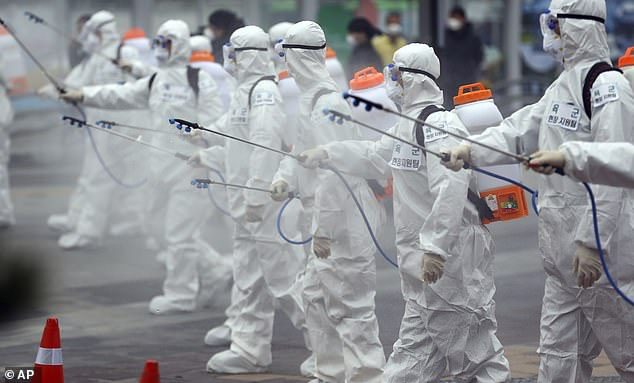 While infection is far more likely to cause severe illness in the elderly, the advice also applies to people of all ages who have serious health conditions (pictured, army soldiers wearing protective suits sprayingdisinfectant in Daegu, South Korea)