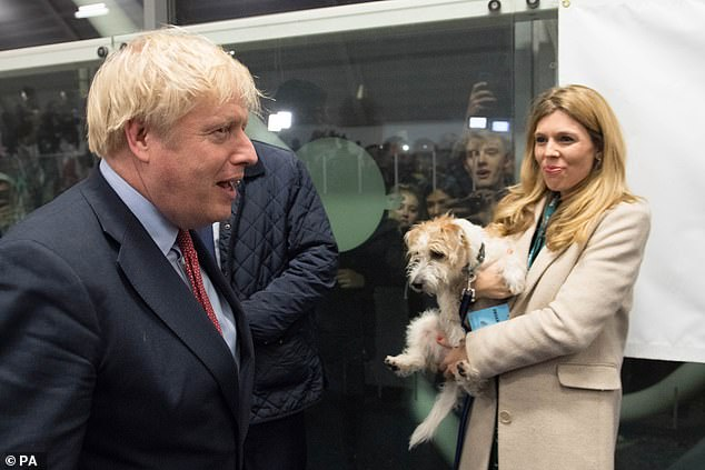 OXBRIDGE TO UXBRIDGE: Clutching Dilyn tightly, Carrie gives Oxford-educated Boris a proud look as they arrive at the Election count in his West London constituency