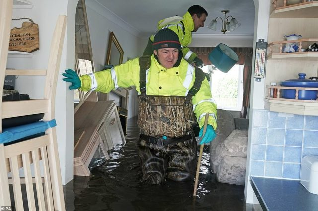 Two rescue workers in Yorkshire try to salvage the remains of people's possessions after flood water devastated the area over the past few weeks
