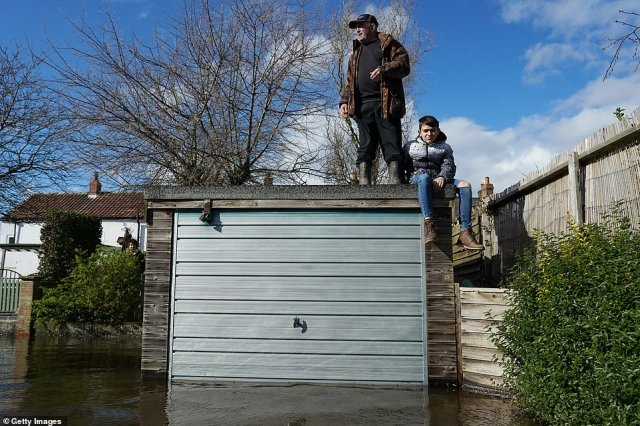 A man and young child stand on a garage to stay dry in East Cowick as water levels rise from the swollen River Aire