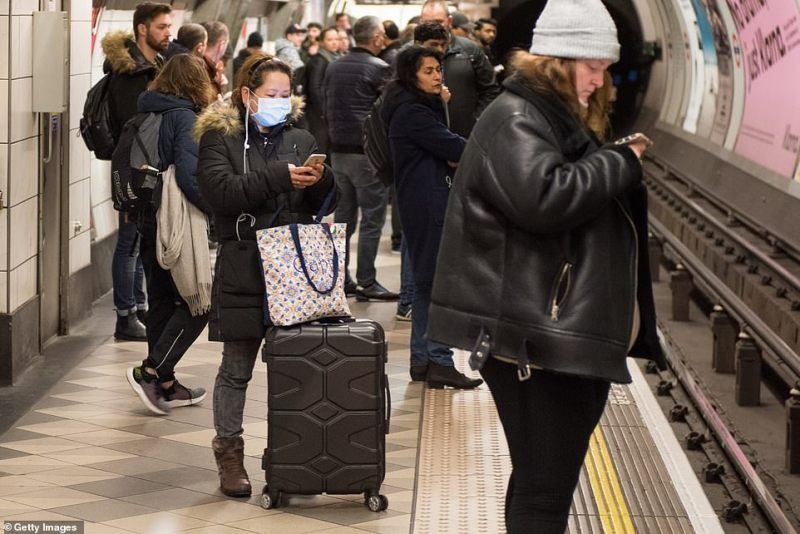 A woman wearing a face mask while waiting for a tube train at Bank underground station today as the number of confirmed cases in Britain hit 35