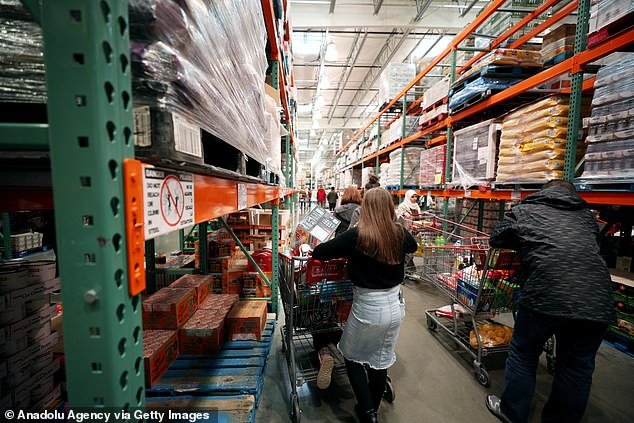 Supermarket shelves are starting to be emptied as people prepare for the spread of coronavirus in New York. Pictured are shoppers on Sunday