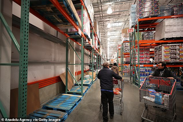 Shoppers rushed to stock-up on essential items at supermarkets across the US. Pictured are customers in New York on Sunday