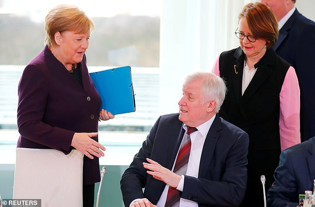 Rejected: German interior minister Horst Seehofer turns away Angela Merkel's offer of a handshake this morning after revealing he had stopped shaking hands over virus fears