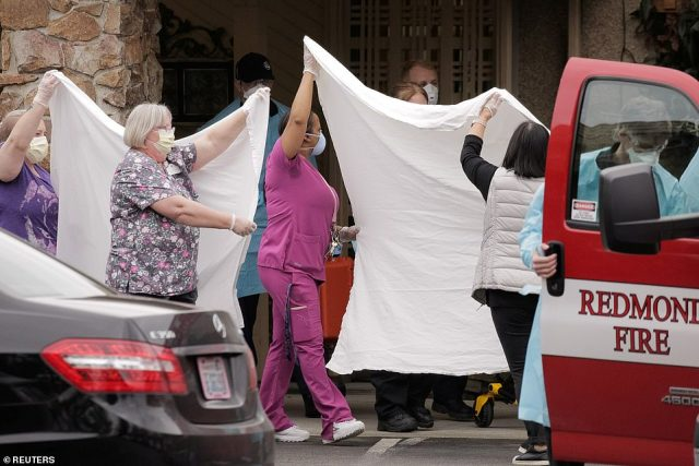 Medics and other healthcare workers transfer a patient on a stretcher to an ambulance at the home on Sunday
