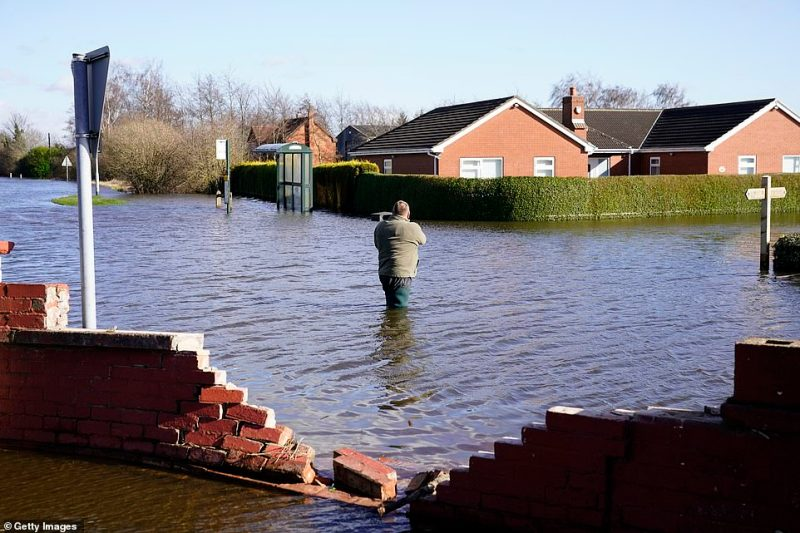 A man walks through floodwaters in the village of East Cowick after the River Aire bursts its banks last week, causing widespread flooding to engulf the community
