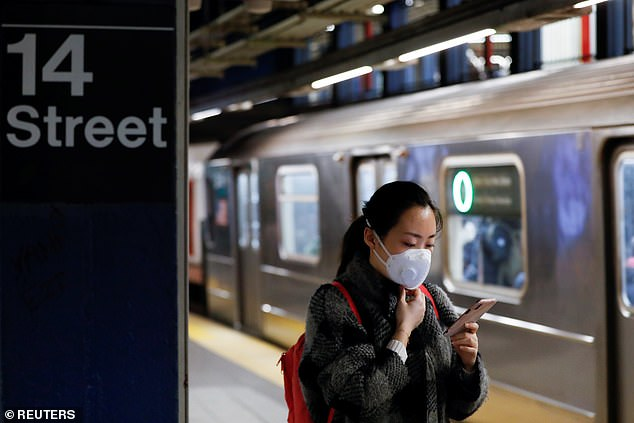 A woman wears a face mask as she waits on the subway after the first confirmed case of coronavirus was announced in New York City