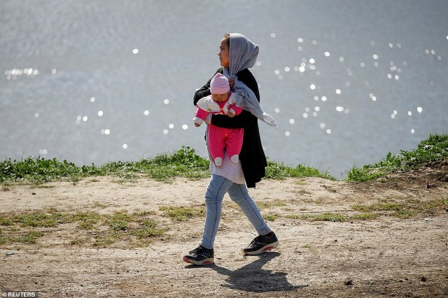 Amigrant woman carries a baby as she walks next to the Tunca river in Edirne, Turkey