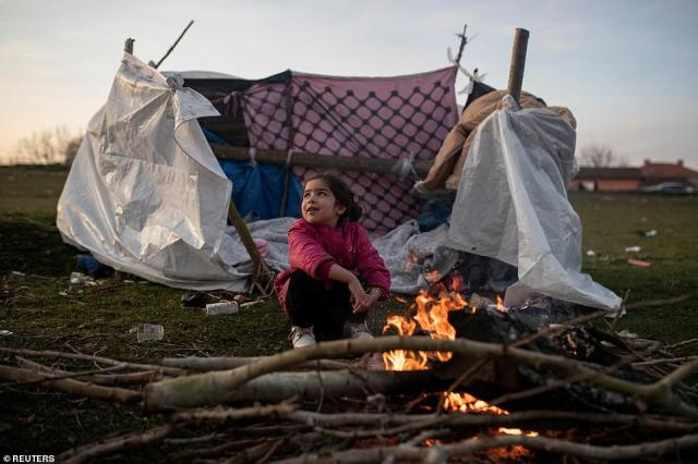 A migrant girl warms herself by the fire near the banks of Evros river, natural border between Turkey and Greece