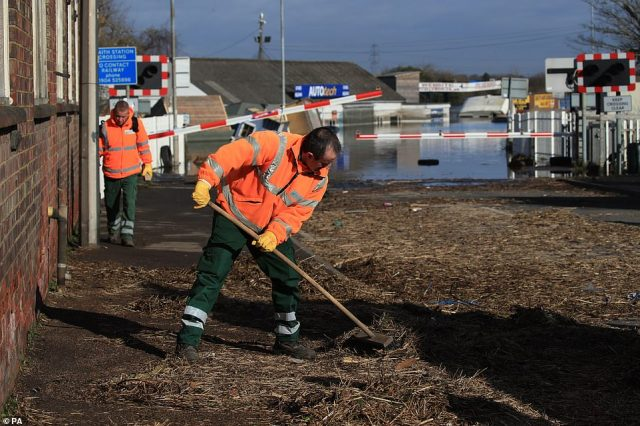 Workmen clear debris from the road where floodwater has begun to recede today in Snaith, East Yorkshire