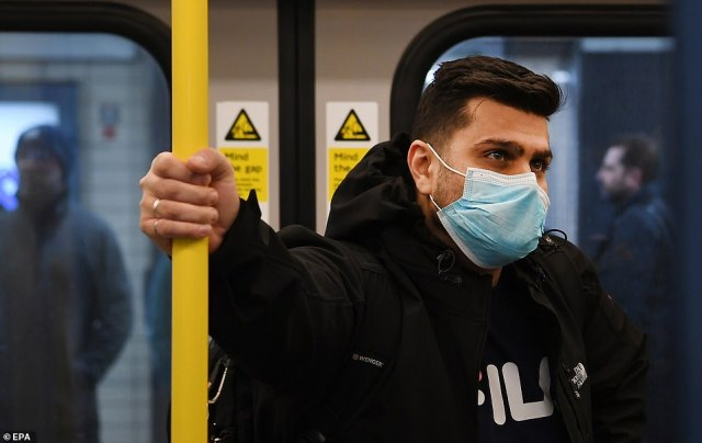 Experts say the virus can live on hard surfaces, such as handles or rails, for hours or even days after it leaves the body. A man is pictured on a train in London wearing a face mask today