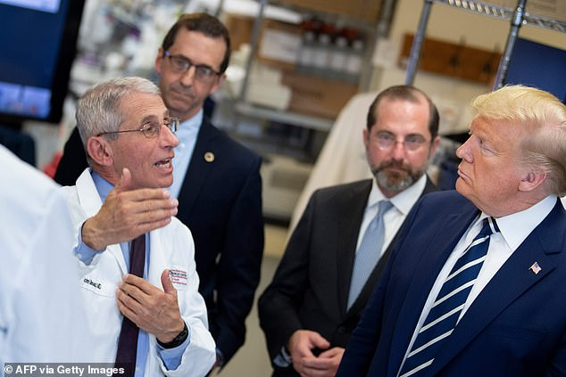 National Institute of Allergy and Infectious Diseases Director Tony Fauci speaks to President Donald Trump during a tour of the National Institutes of Health's Vaccine Research Center