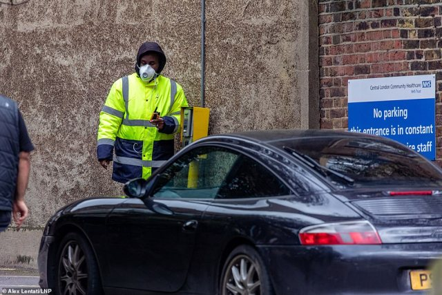 A security guard with a mask on checks a driver at a coronavirus drive-thru testing centre at Parsons Green Health Centre in Fulham