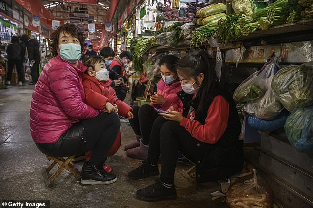 Chinese vegetable vendors wear protective masks as they wait for customers at a local market
