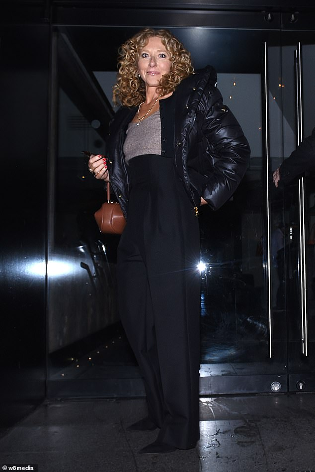 Effortlessly chic:Kelly looked stunning in a beige jumper that she tucked into high-waist black trousers for the event