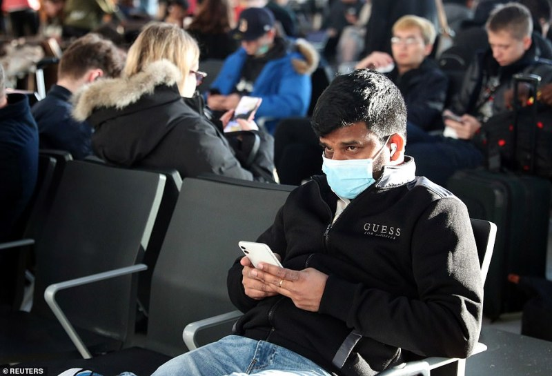 BA did not reveal where the baggage handler worked, but Heathrow said in a statement: 'The welfare of our passengers and colleagues is our top priority. Pictured are passengers at Terminal 5 wearing masks on Friday