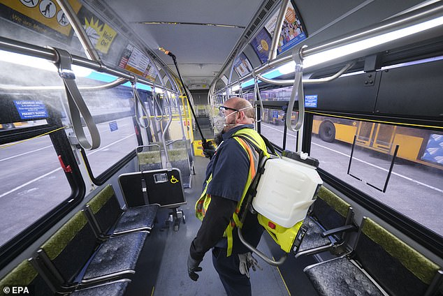 King County Metro equipment service worker Raymond Determann sprays the interior of a King County Metro Transit bus with disinfectant cleaner in response to the outbreak