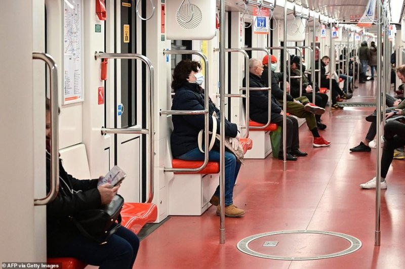 Commuters, some wearing respiratory masks, travelling in the underground metro in downtown Milan while sat the recommended 3ft distance from each other