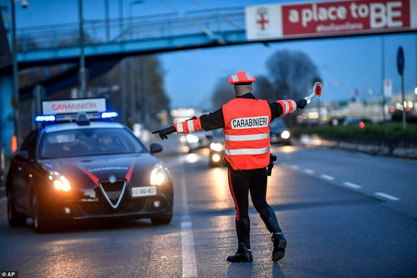 A police officer checks the cars entering Milan last night with drastic new travel restrictions to stop the spread of the virus