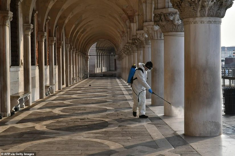A porch near the Doge's Palace in Venice is now deserted, except for a healthcare professional who sprays disinfectant