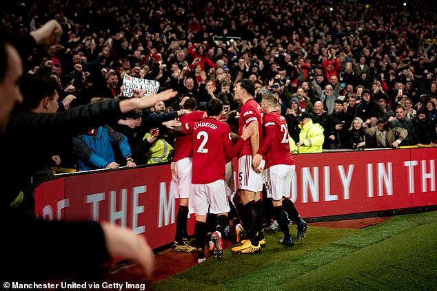 Manchester United players pictured celebrating with their fans after beating rivals City